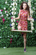 Smiling woman stands next swing overgrown with flowers
