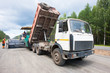 Lorry unloading asphalt into tracked paver during roadworks