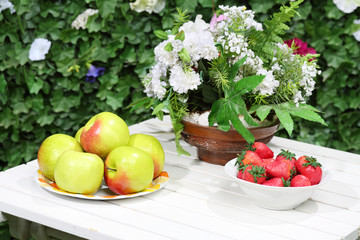 Plates with apples, strawberries and flowers on white table.