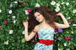 Beautiful woman with curly hair stands next to green hedge