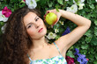 Beautiful brunette woman with apple next to green hedge