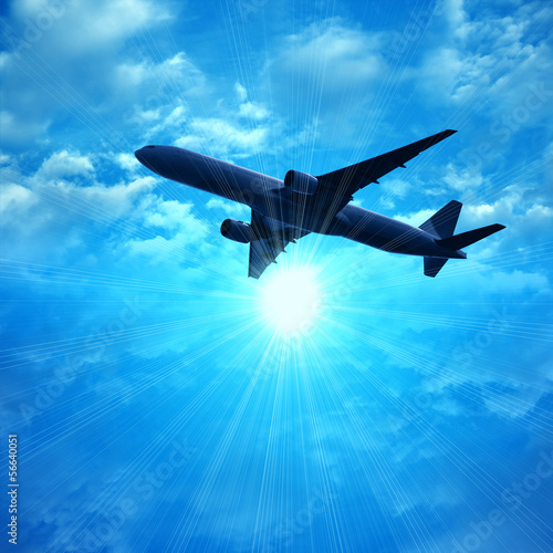 dark silhouette of airplane flying over blue sky background