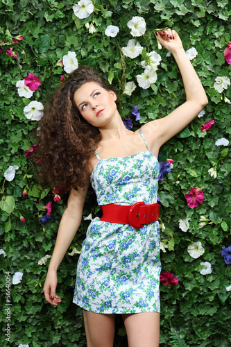 Beautiful dreaming woman with curly hair stands