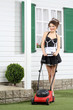 Beautiful smiling housemaid stands with lawn mower near house