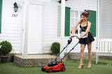 Beautiful smiling housemaid mows lawn by mower