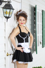 Beautiful young housemaid stands near front door