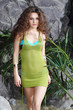 Beautiful woman in swimsuit and green jersey walks near rocks