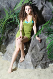 Beautiful woman in swimsuit and green jersey sits on stone
