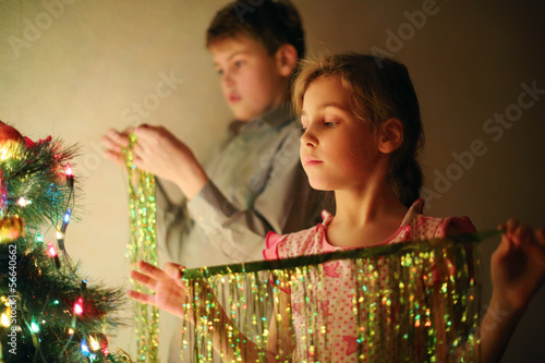 Girl and boy decorated Christmas tree with tinsel at evening