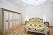 Luxurious bedroom with gilt double bed and wardrobe