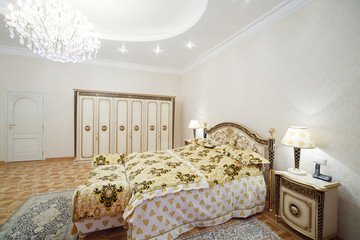 Luxurious bedroom with gilt double bed and bedside tables