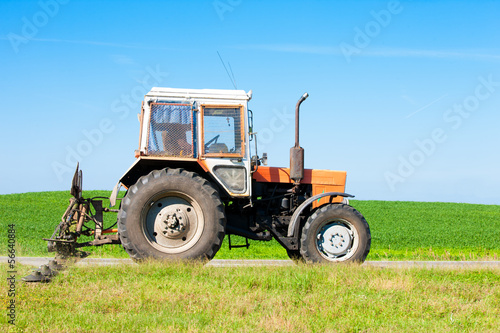 Tractor with grass cutter mowing lawn along road