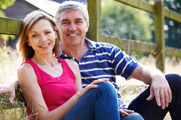 Romantic Middle Aged Couple Relaxing On Walk In Countryside