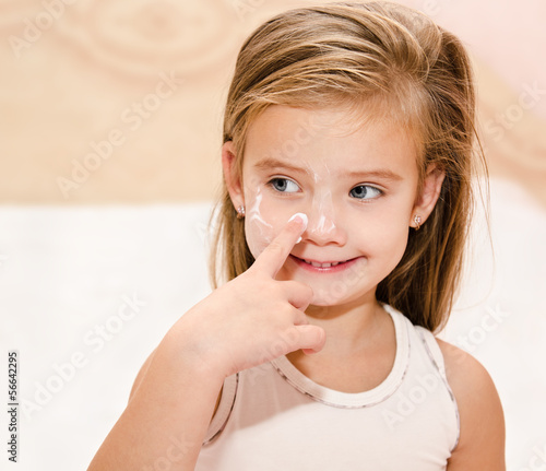 Cute little girl  applying cream
