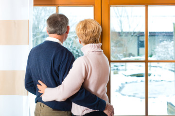 Senior couple looking or of the window hugging