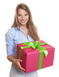 Beautiful woman with christmas gift in her hands
