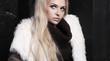 Beautiful blond woman in fur near bricks wall.winter fashion.