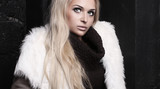 Beautiful blond woman in fur near bricks wall.winter fashion.