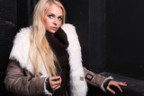 Beautiful blond woman in a fur.winter style.stone background