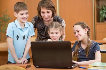 schoolchildren and teacher using laptop at lesson