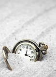 Antique pocket watch buried in sand