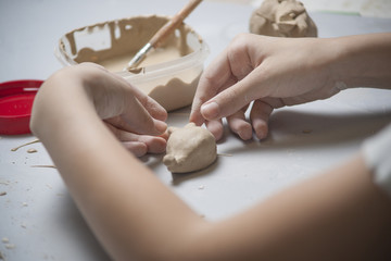 Girl make toyfrom clay