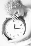Conceptual portrait of woman in bed with big clock, b/w photo.