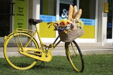 vecchia bicicletta gialla con pane e fiori sul cestino