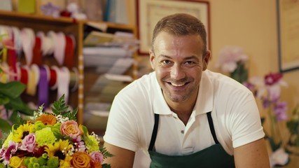 happy man working as florist in flower shop