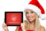 girl in a red Christmas hat on New Year holding tablet with chri