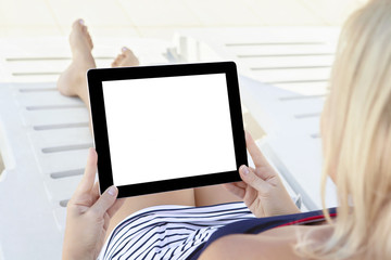girl in a bathing suit lying on a chaise lounge with a computer