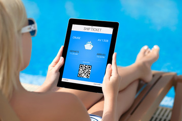 girl lying on a deck chair by the pool and holding a tablet with