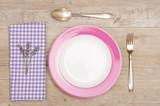 Messer, Gabel und Teller auf rustikalen Tisch aus Holz