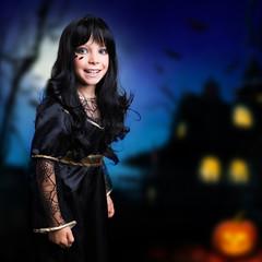 kleines Mädchen im Hexenkostüm vor Hexenhaus