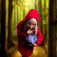 kleines Mädchen mit rotem Umhang im Wald