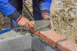 Man laying concrete block and bricks wall 2