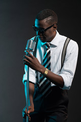 Retro african american jazz singer with microphone. Wearing shir