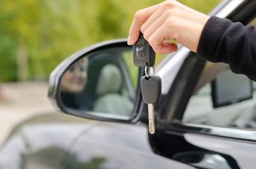 Woman holding car keys outside the vehicle