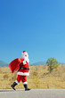 Santa claus with bag walking on an open road