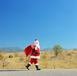 Full length portrait of a santa claus with bag walking on a road