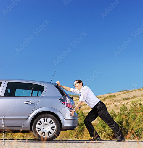 Young businessman pushing his car with empty fuel tank