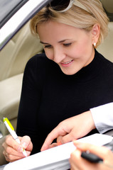 Woman signing a deal to purchase a car