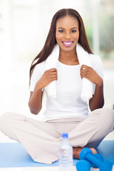 african woman sitting on mat after working out