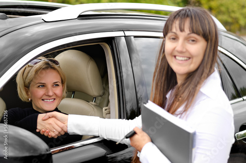 Saleslady shaking hands with a customer