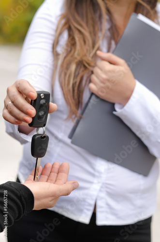 Saleswoman handing over the keys to a car