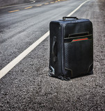 lone suitcase stands in the middle of the road