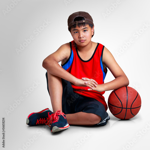 Teenager boy sitting with basketball