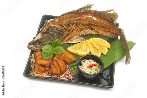 Fish fried with spicy mango salad in the black plate