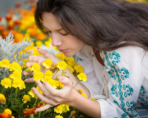 Young beautiful woman smelling yellow flowers in garden.