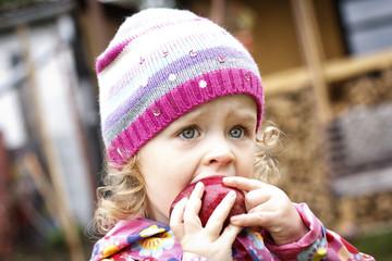 Little girl eating apple in autumn